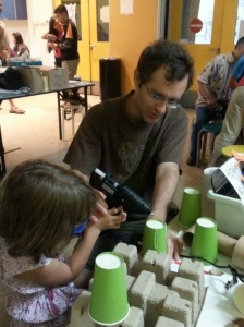 Father and Daughter using the hot glue gun to glue junk together.