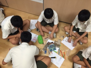 Grup boys trying out paper circuit